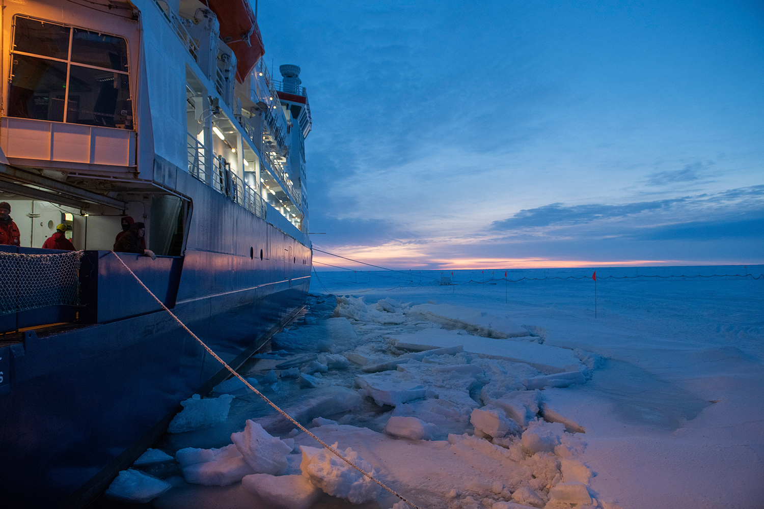Beautiful sunrise scenery in the Arctic landscape. A giant icebreaker vessel in front is faces the light, stuck in the ice.
