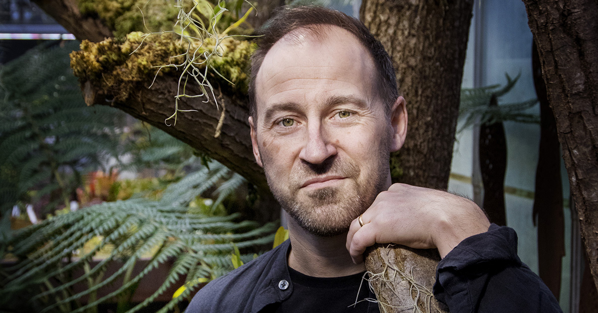 Portrait photo of Johan Eklöf dressed in black clothes and standing among exotic plants and trees