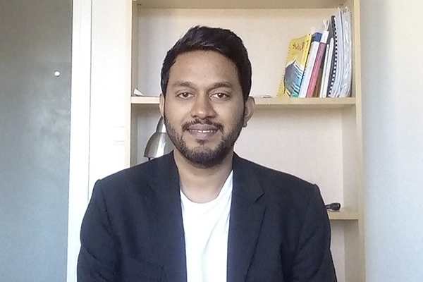 Portrait photo of Kosala Amarasinghe, dressed in a suit and sitting in front of a book shelf.